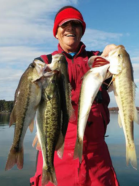 Capt. Gus shows a limit of spotted bass before being released alive.